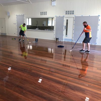 Applying oil to timber floor inside hall